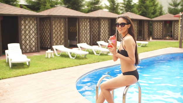 Graceful model holding a glass of juice while resting in the luxury hotel. side view photo. beverage and weekend concept