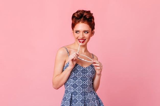 선글라스와 함께 포즈를 취하는 우아한 red-haired 소녀. 미소로 핑크 공간에 고립 된 즐거운 생강 여자의 스튜디오 샷.