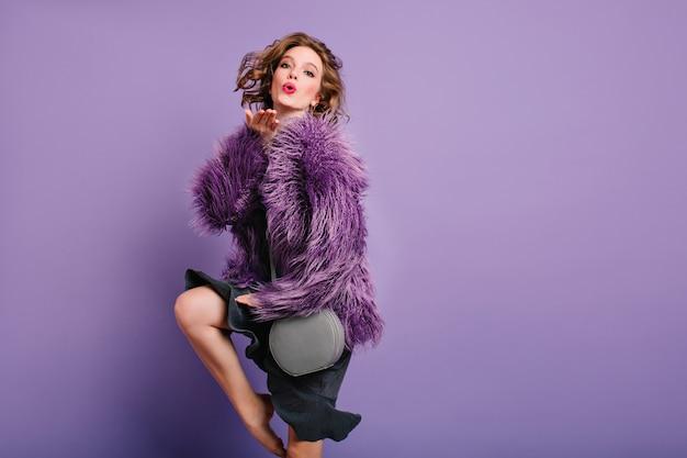Graziosa ragazza romantica manda un bacio d'aria su sfondo viola e balla