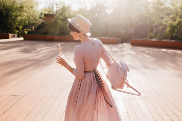 Graceful shapely girl in retro dress dancing outdoor under sunlight, holding trendy backpack