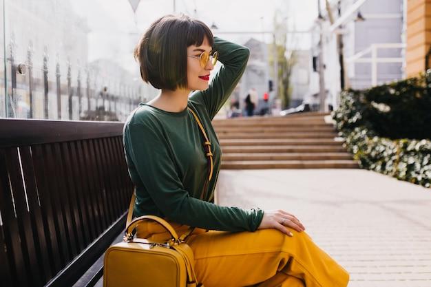 야외 휴식 선글라스에 우아한 짧은 머리 소녀. 화창한 날에 벤치에 포즈 녹색 스웨터에 사랑스러운 여자.