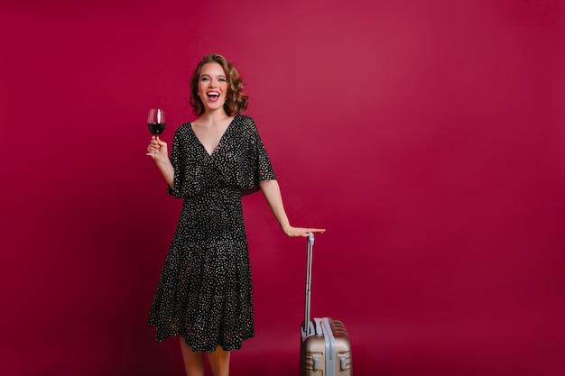 Graziosa donna dai capelli corti con un bicchiere di champagne in posa su sfondo scuro e ridendo