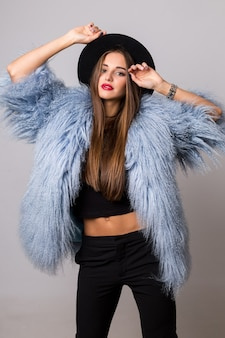 Graceful skinny  woman in stylish winter fluffy  blue coat and black hat posing on bright  grey wall.