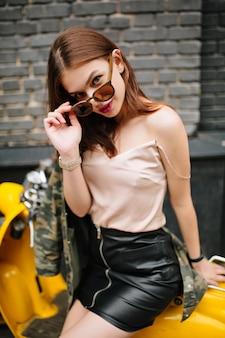 Изящная стройная девушка с интересом смотрит, снимая стильные солнцезащитные очки, сидя на желтом мопеде