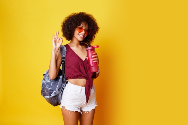 Graceful sport black female standing on yellow and holding pink bottle of water wearing stylish summer clothes and back pack.
