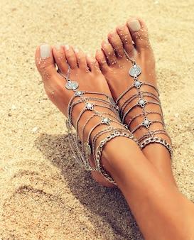自由奔放に生きるスタイルの銀のブレスレットで覆われた優雅な日焼けした女性の足が黄色い砂の上に横たわっています
