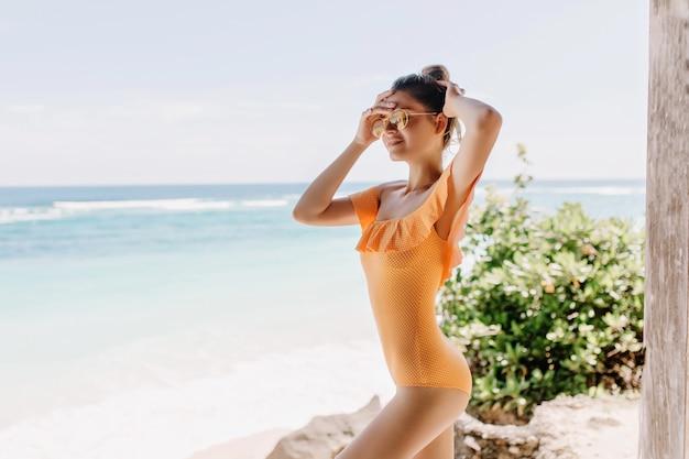ビーチでポーズをとる黄色い服を着た優雅な白人女性モデル。目を閉じて海の近くで冷やしているオレンジ色の水着のスリムな白人の女の子。