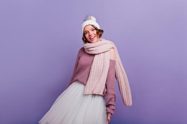 紫色の壁に立っている長く暖かいスカーフの優雅な白人の女の子。笑顔でポーズをとって帽子をかぶった洗練された喜んで若い女性。