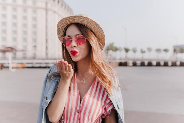 街にエアキスを送る縞模様のドレスを着た優雅な白人の女の子。春の日に愛を表現する麦わら帽子の魅力的な若い女性。