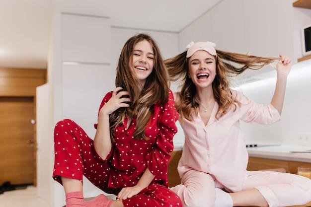 Изящная белая девушка с вьющейся прической, наслаждаясь добрым утром с сестрой. крытый снимок вдохновленных кавказских женщин-моделей в ночных костюмах, играющих со своими волосами.