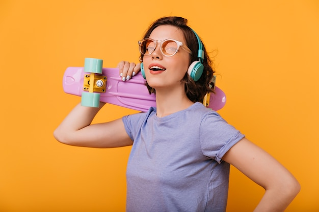 Graziosa ragazza bianca con lo skateboard sognante che guarda lontano. ritratto dell'interno di bella donna dai capelli corti in cuffie blu.