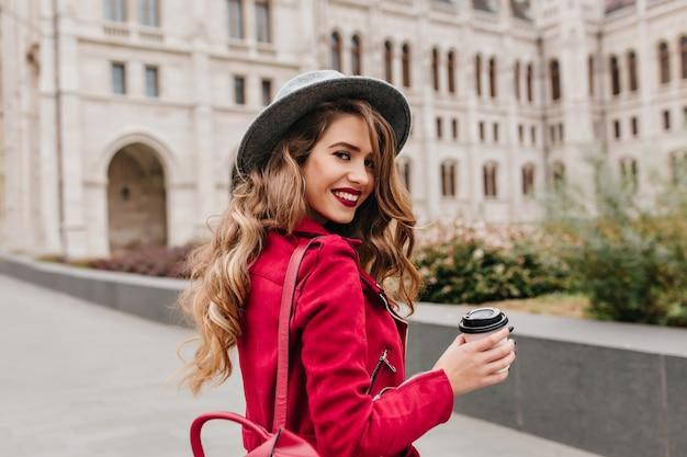 Graziosa donna bianca con cappello grigio guardando sopra la spalla mentre esplorava la parte vecchia della città