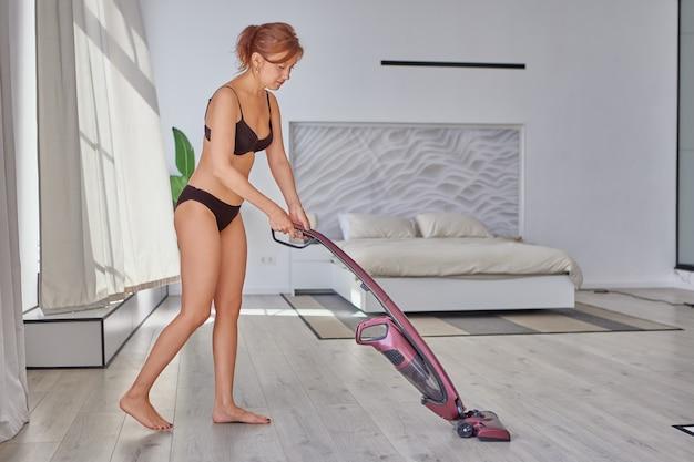 ランジェリー掃除機の寝室の床の優雅な白人女性
