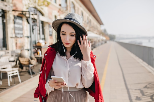 Graceful white woman looking at phone while spending time outdoor