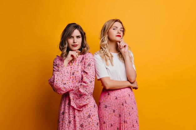 우아한 백인 여성 재미 노란색 벽에 포즈. 분홍색 옷을 입은 멋진 자매들이 함께 차갑습니다.