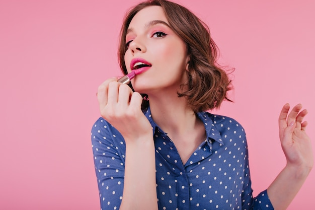 Graceful woman doing lips makeup on bright wall. indoor portrait of magnificent short-haired girl posing with lipstick.