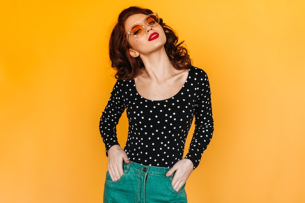Graceful woman in green pants standing with hands in pockets. studio shot of ginger girl isolated on yellow space.