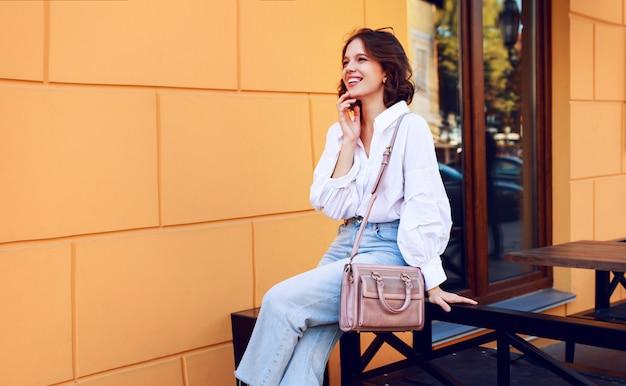 黄色の壁のモダンなカフェのそばに座ってカジュアルな服装で優雅な女性。おしゃれな表情。前向きな気分。
