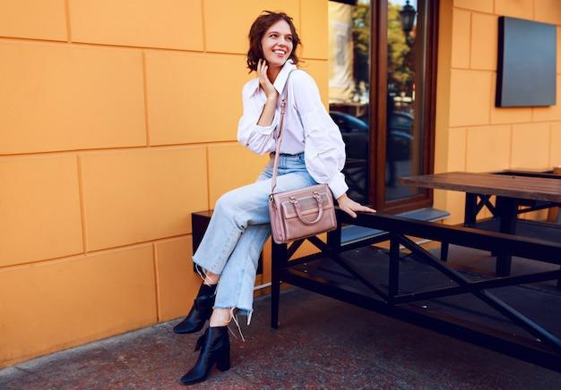 노란색 벽과 현대적인 카페 근처에 앉아 캐주얼 복장에 우아한 여자. 세련된 모양. 긍정적 인 분위기.