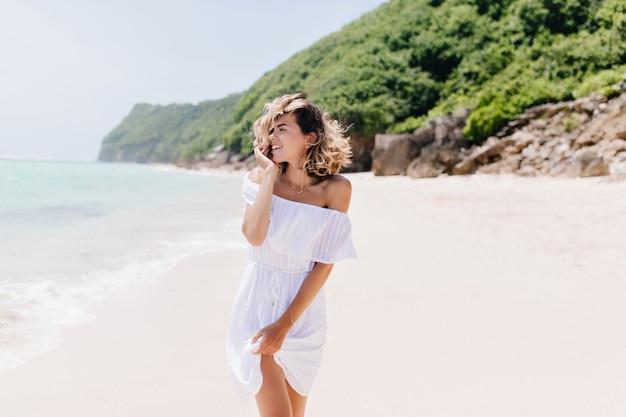 밝은 미소로 바다를 바라 보는 드레스에 우아한 여자. 열대 섬에서 시간을 보내는 화려한 금발 아가씨의 야외 사진.