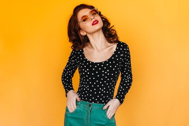 ポケットに手を入れて立っている緑のズボンの優雅な女性。黄色い空間に隔離された生姜少女のスタジオショット。