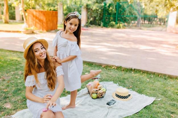 彼女のかわいい娘が彼女の後ろで踊っている間、公園の毛布の上に座っている白いドレスを着た優雅な女性。ピクニックの後に楽しんでいる2人の楽しい姉妹の屋外の肖像画。