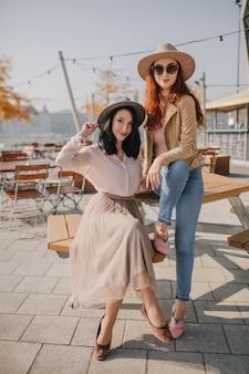 Graceful woman in long skirt sitting in street cafe with best friend