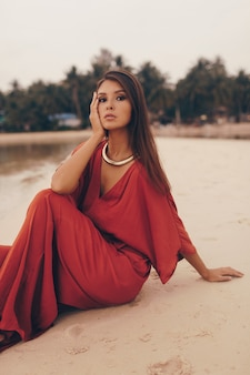 Graceful woman posing on the beach, sitting on sand in red dress