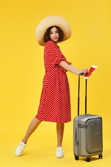Graceful woman in red dress with gray suitcase going traveling on yellow background.