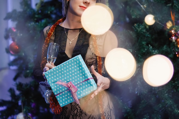 Graceful woman rejoices with a gift box near a christmas tree. a woman laughs, smiles, poses. special vintage noise and grain filter, blurry lights.