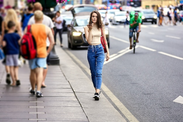 Изящная женщина разговаривает по смартфону на людной улице возле движения