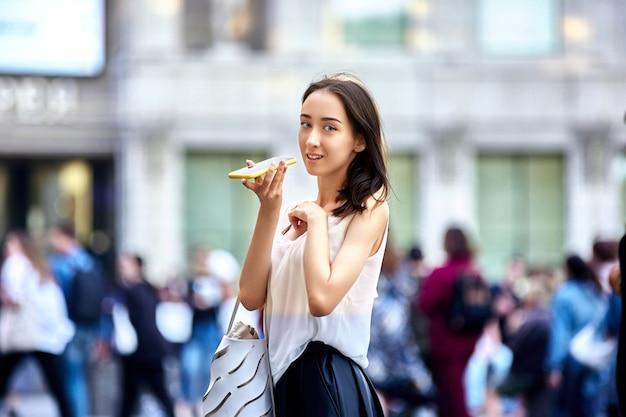 도시를 걷는 동안 스마트폰으로 이야기하는 우아한 여성