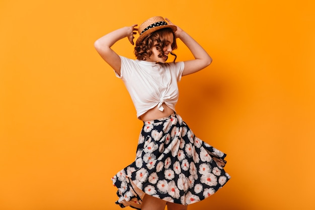 Graceful woman in trendy skirt dancing with hands up. studio shot of romantic curly girl having fun on yellow background.