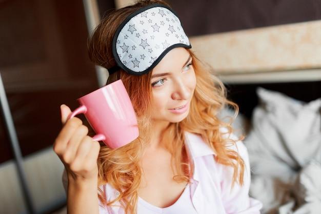 彼女の寝室のアイマスクでポーズをとって、熱いお茶を飲んで率直な笑顔で優雅な女性。