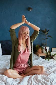 화려한 머리를 가진 우아한 여성은 침대에서 머리 위의 나마스테에 손을 잡고 명상한다