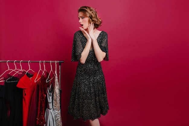 Graceful woman with worried face expression choosing outfit for romantic date