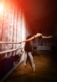 검은 드레스를 입은 우아한 젊은 발레리나가 발끝으로 서서 스튜디오 배경에서 뒤로 구부리고 있습니다. 사진은 고전 발레 예술의 비교할 수없는 아름다움을 크게 반영합니다.