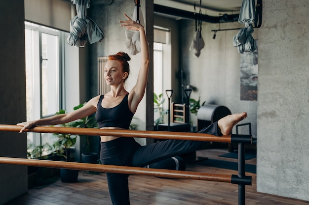 Graceful young concentrated fit female ballerina or dancer wearing black sports bra and leggings stretching by doing splits using ballet barre during pilates class in studio. healthy sportive people