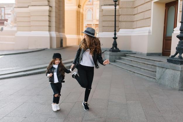 Изящная молодая кудрявая женщина в черных обтягивающих джинсах смешно танцует на улице возле радостной маленькой девочки.