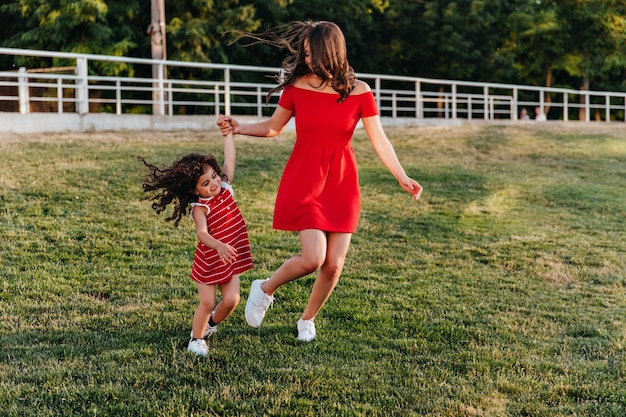 Graceful young lady in short red dress holding hands with daughter. outdoor full-length photo of mother and child playing in park.