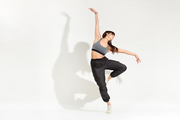 클래식 댄스를 수행하는 힙합 복장에 우아한 젊은 여자 댄서 흰색 스튜디오 배경에 예술적 그림자와 함께 한쪽 다리에 균형을 뻗은 팔 포즈