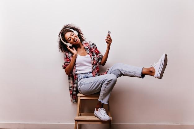 白で音楽を聴いているブルージーンズの優雅な若い女性。目を閉じて笑っているヘッドフォンでのんきなアフリカの女の子の屋内ショット。