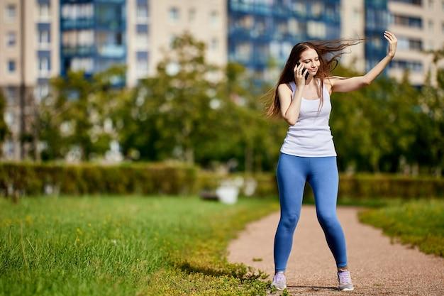 Изящная молодая женщина разговаривает по смартфону в парке