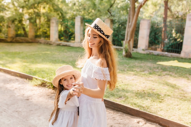 Graceful young woman in white dress dancing with daughter on the alley and smiling. outdoor portrait of charming mom in straw boater holding hands with joyful child wanted to play.