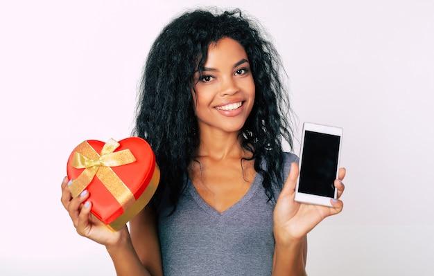 Милосердная африканская этническая женщина с эффектной улыбкой смотрит в камеру и держит в правой руке красную коробку в форме сердца, а в левой - смартфон.