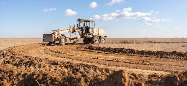 A grader machine making a new road, dig the gravel dirt in the field