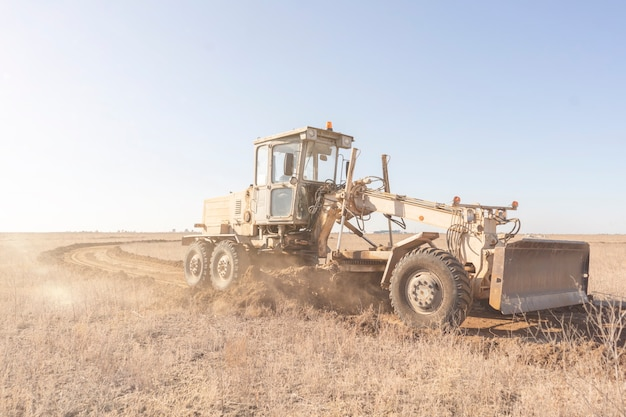 A grader machine making a new road, dig the gravel dirt in the field Premium Photo