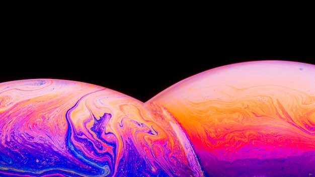 Gradient artistic colorful saturated soap bubbles on black background