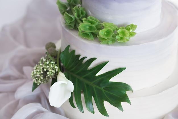 Градиент сирени с белым свадебным многоуровневым тортом с цветами и зелеными пальмовыми листьями