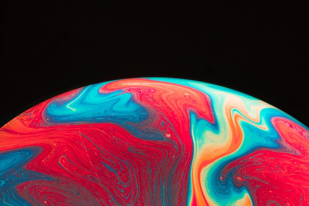 Gradient multicolored rippled soap bubble on black background